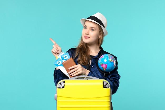 Giovane donna di vista frontale che tiene i biglietti e il globo sul viaggio di vacanza del mare di viaggio aereo del fondo blu