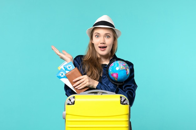 Front view young woman holding tickets and globe on the blue background plane voyage sea vacation journey