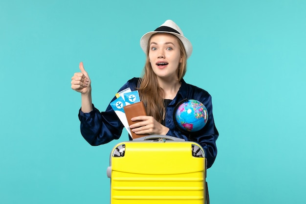 Front view young woman holding tickets and globe on blue desk plane sea vacation journey voyage