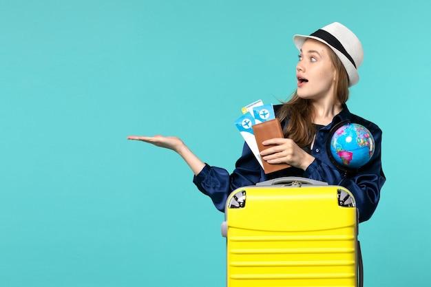 Vista frontale della giovane donna che tiene i biglietti e il globo sul viaggio di viaggio di vacanza del mare dell'aereo di sfondo azzurro