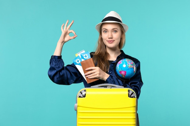 Front view young woman holding tickets and globe on light blue background plane sea vacation journey voyage