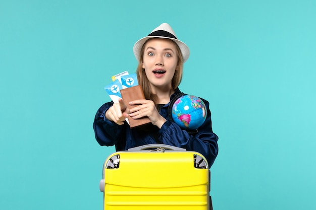 Front view young woman holding tickets and globe on light-blue background plane voyage sea vacation journey
