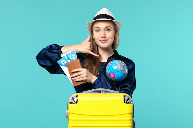 Front view young woman holding tickets and globe smiling on blue background plane sea vacation journey voyage