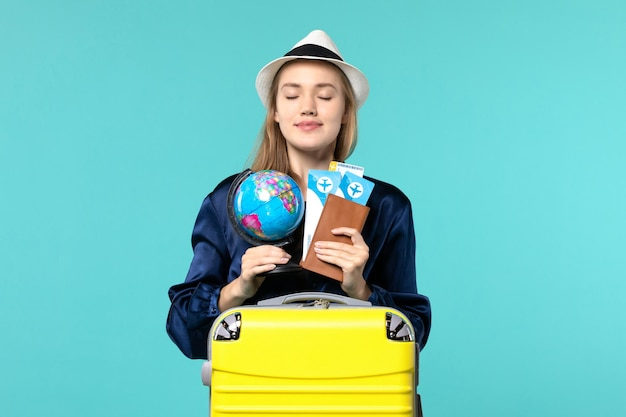Front view young woman holding tickets and little globe on blue background plane female vacation journey voyage sea