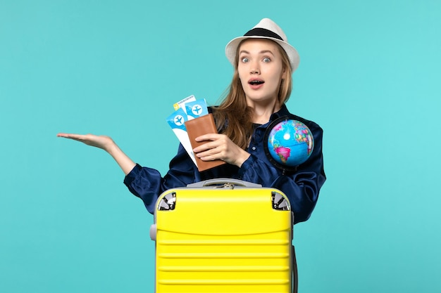Front view young woman holding tickets and little globe on blue background plane sea vacation journey voyage
