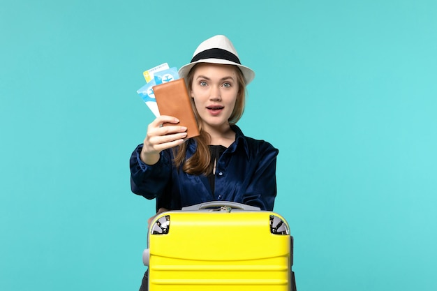 Front view young woman holding tickets and preparing for trip on blue background journey sea vacation travel plane voyage