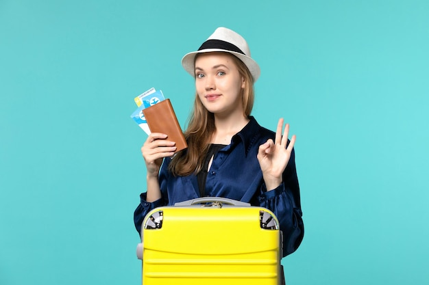 Front view young woman holding tickets and preparing for trip on the blue background journey sea vacation travel plane voyage