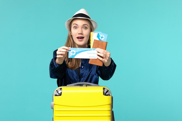 Front view young woman holding tickets and preparing for trip on the blue background journey voyage plane sea vacation travel