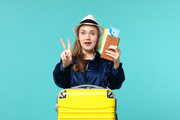 Front view young woman holding tickets and preparing for trip on blue desk journey sea vacation travel plane voyage