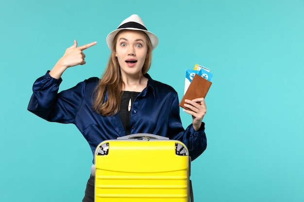 Front view young woman holding tickets and preparing for trip on blue desk journey voyage plane sea vacation travel