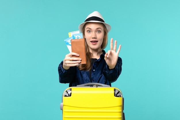 Vista frontale della giovane donna che tiene i biglietti e si prepara per il viaggio su sfondo azzurro viaggio mare vacanza viaggio viaggio aereo