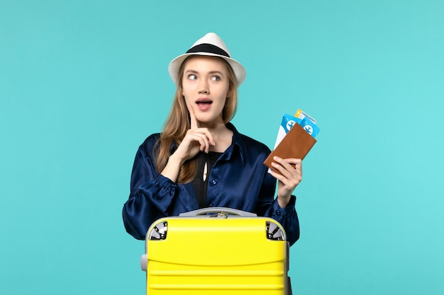 Front view young woman holding tickets and preparing for trip on light-blue background journey voyage plane sea vacation travel