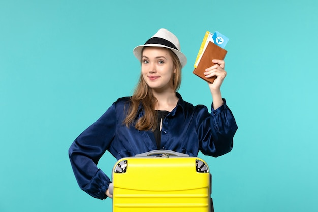 Front view young woman holding tickets and preparing for vacation on a blue background journey sea vacation travel plane voyage
