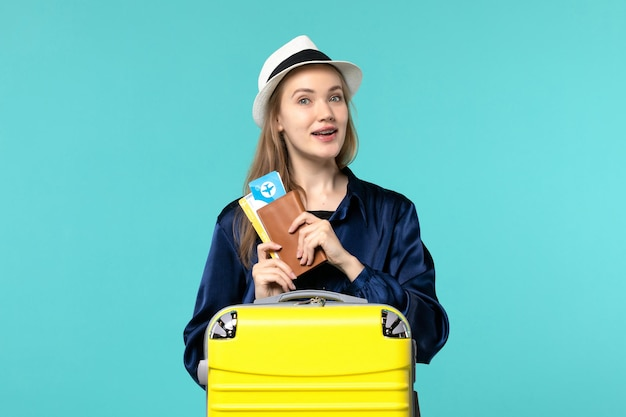 Front view young woman holding tickets and preparing for vacation on a blue background plane journey sea vacation voyage travel