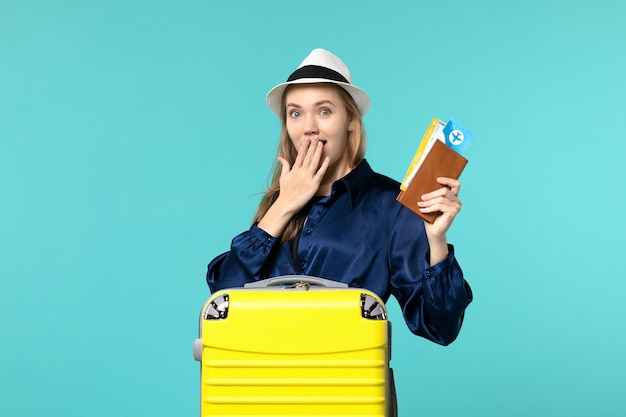 Front view young woman holding tickets and preparing for vacation on blue background plane journey sea vacation voyage travel