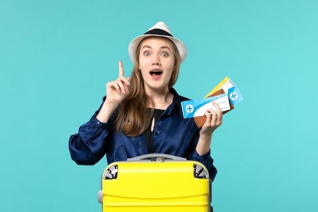Giovane donna di vista frontale che tiene i biglietti e che si prepara per la vacanza sulla vacanza di aereo di viaggio di viaggio del mare dello scrittorio blu