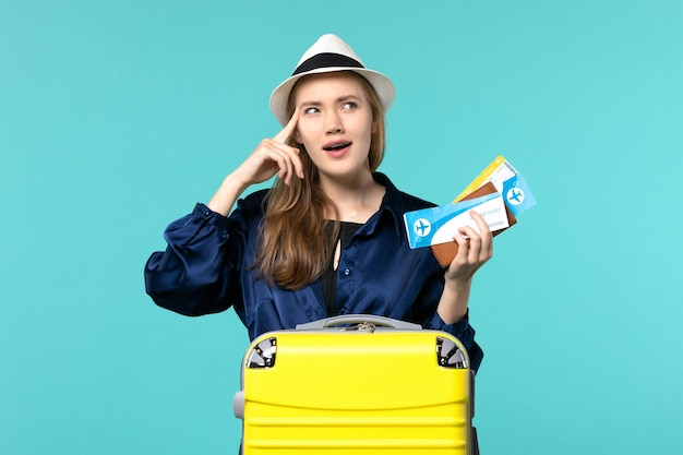 Front view young woman holding tickets and preparing for vacation on light-blue background sea journey voyage plane vacation