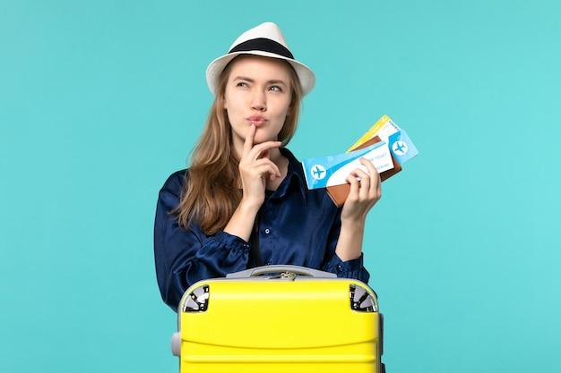 Vista frontale della giovane donna che tiene i biglietti e si prepara per la vacanza pensando su sfondo blu viaggio mare viaggio aereo vacanza