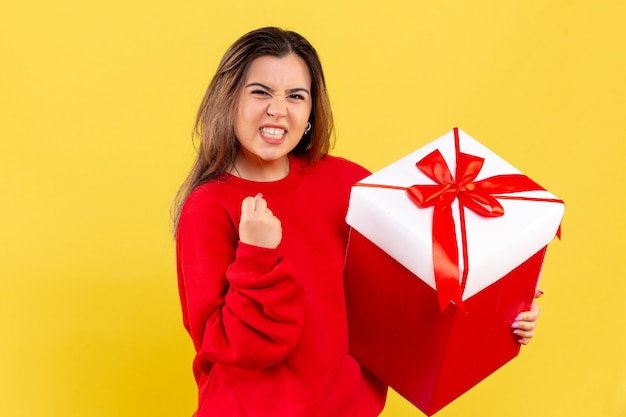 Вид спереди молодая женщина, держащая рождественский подарок на желтом фоне
