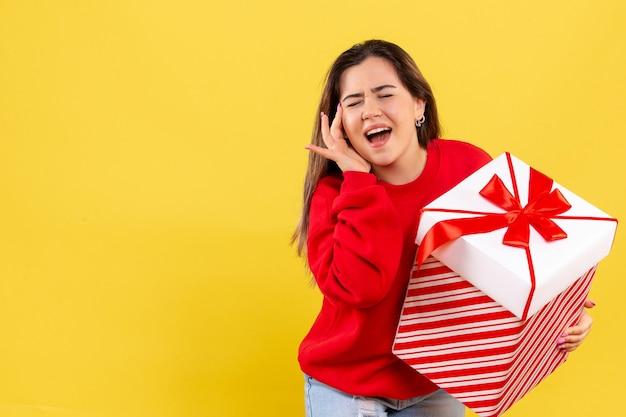 黄色の背景にクリスマスプレゼントを保持している正面図若い女性