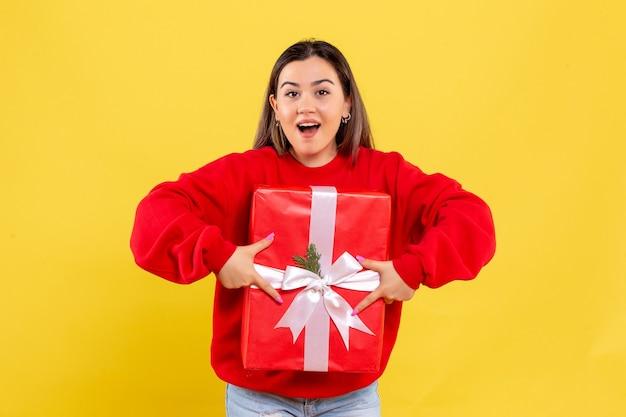 Giovane donna di vista frontale che tiene il regalo di natale su fondo giallo