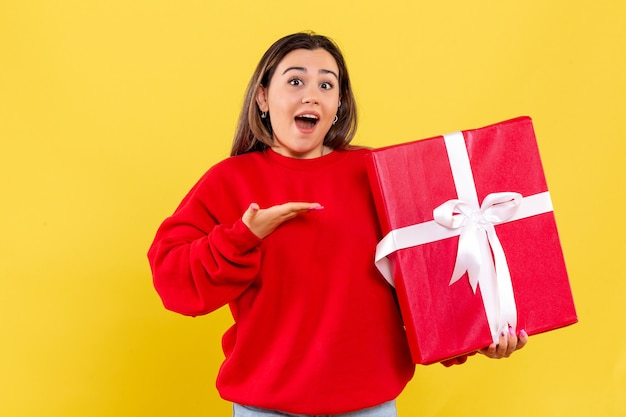 Front view young woman holding xmas gift on yellow background