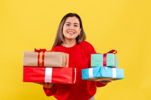 Вид спереди молодая женщина, держащая рождественские подарки на желтом фоне