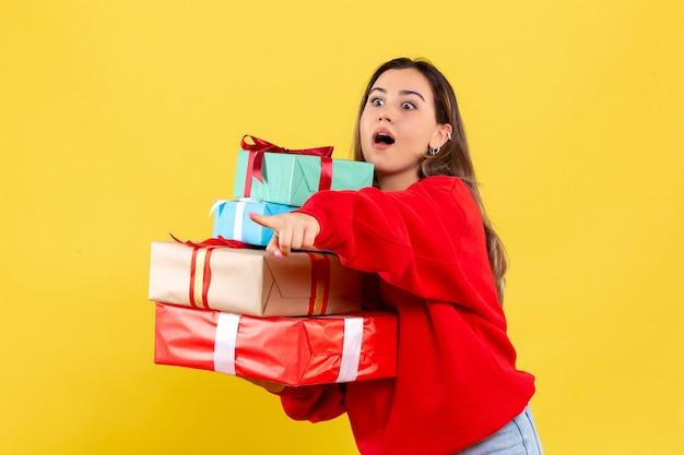 Giovane donna di vista frontale che tiene i regali di natale su fondo giallo