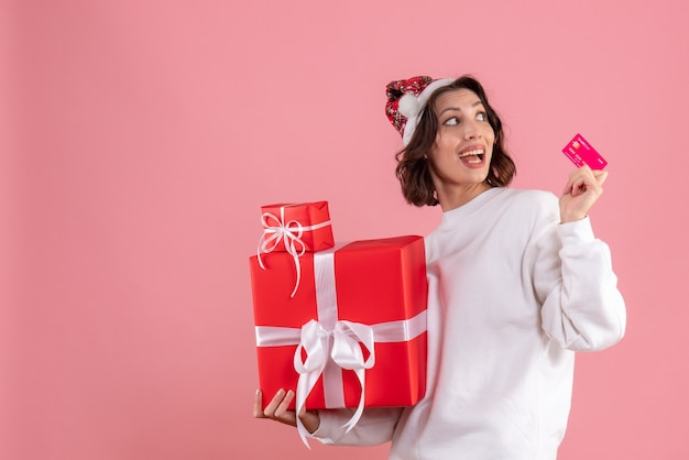 Front view of young woman holding xmas presents and bank card on pink wall