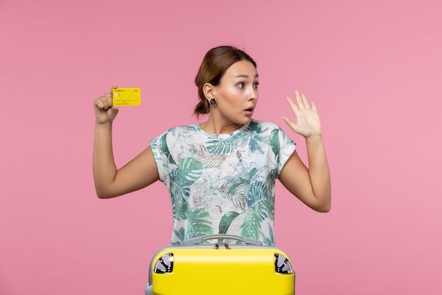 Vista frontale della giovane donna che tiene la carta di credito gialla sul muro rosa chiaro