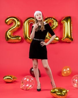 赤いクリスマス写真に黒いドレスの風船を着た正面の若い女性
