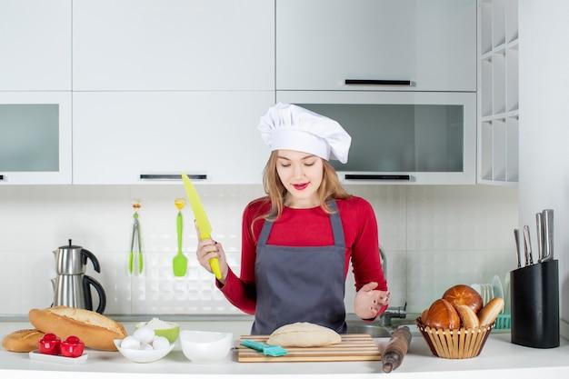 부엌에서 녹색 칼을 들고 요리사 모자와 앞치마에 젊은 여자의 전면 보기