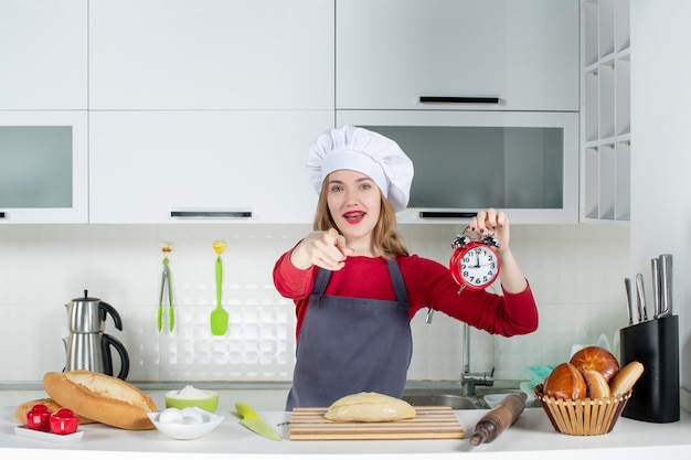 キッチンのカメラを指している赤い目覚まし時計を保持しているクック帽子とエプロンの正面図若い女性