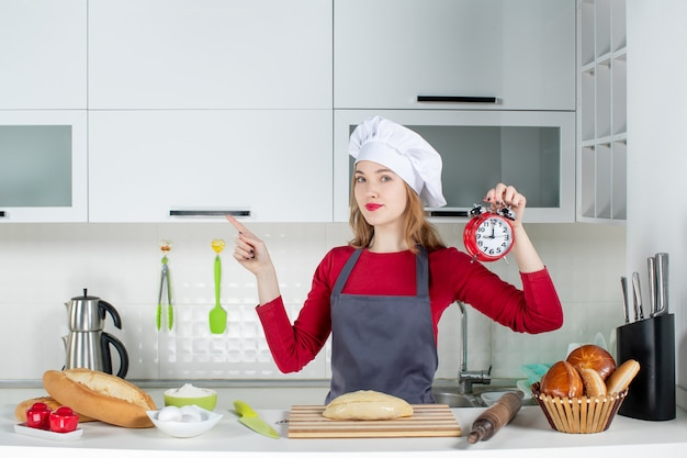 キッチンの左を指す赤い目覚まし時計を保持しているクック帽子とエプロンの正面図若い女性