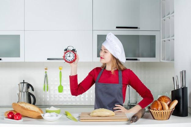 Вид спереди молодая женщина в поварской шляпе и фартуке держит красный будильник, положив руку на талию на кухне