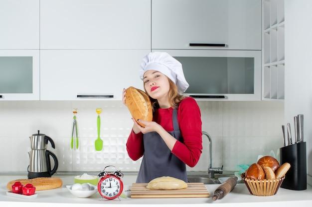 Вид спереди молодая женщина в поварской шляпе и фартуке, подняв хлеб на кухне