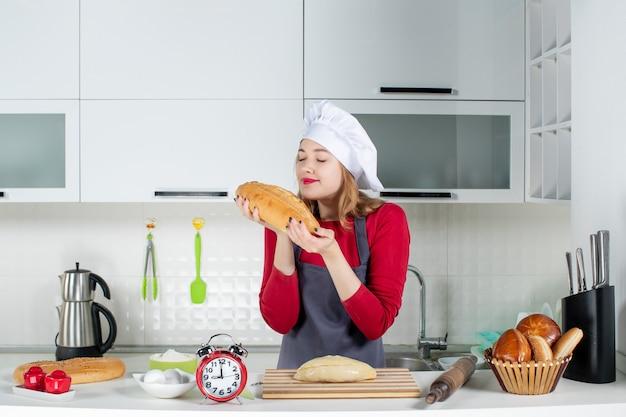 キッチンでパンの匂いを嗅ぐクックハットとエプロンの若い女性の正面図