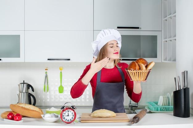 料理の帽子とエプロンの匂いがするパンをキッチンで正面から見た若い女性