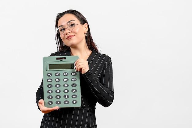 白い背景の美しさのビジネスオフィスの仕事のファッションに大きな計算機を保持している暗い厳格なスーツの正面図若い女性