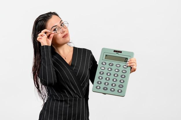 白い背景の上の大きな計算機を保持している暗い厳格なスーツの正面図若い女性美容女性ファッションビジネスオフィスの仕事