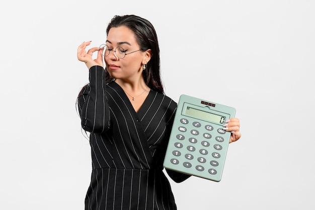 白い机の上の大きな計算機を保持している暗い厳格なスーツの正面図若い女性美容女性ファッションビジネスオフィスの仕事