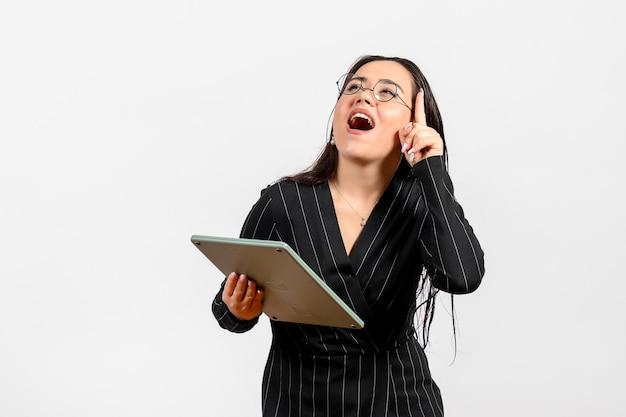 白い机の上の巨大な計算機を保持している暗い厳格なスーツの正面図若い女性仕事女性女性美容ファッションビジネス