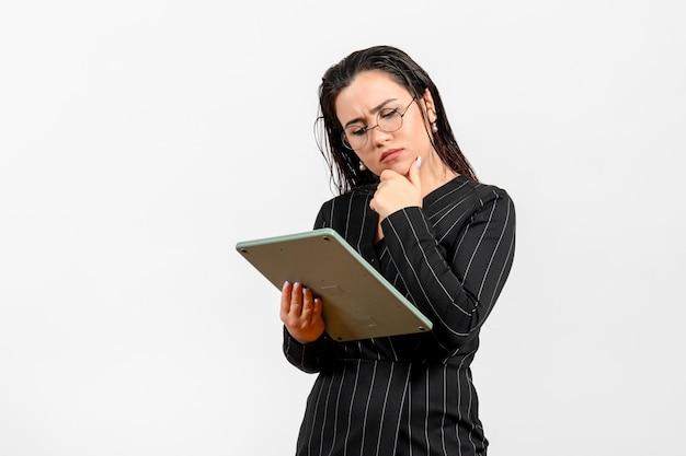 白い床の仕事の女性の女性の美容ファッションビジネスで巨大な計算機を保持している暗い厳格なスーツの正面図若い女性