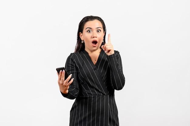正面図白い背景の上のショックを受けた顔を持つ電話を保持している暗い厳格なスーツの若い女性女性女性ファッションサラリーマン仕事の美しさ