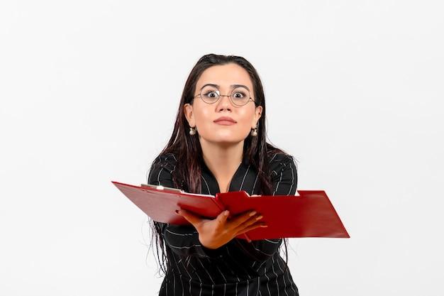 흰색 배경 사무실 비즈니스 직업 패션 여성 문서에 빨간색 파일을 들고 어두운 엄격한 정장에 전면보기 젊은 여자