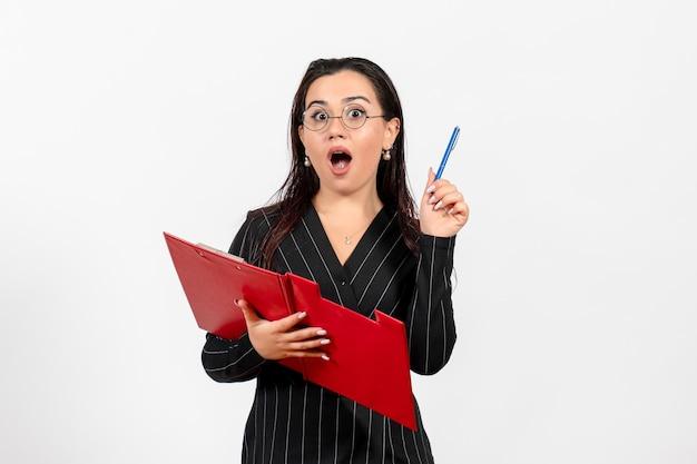 白い背景の上の赤いファイルを保持している暗い厳格なスーツの正面図若い女性オフィス美容ビジネス仕事ファッション女性