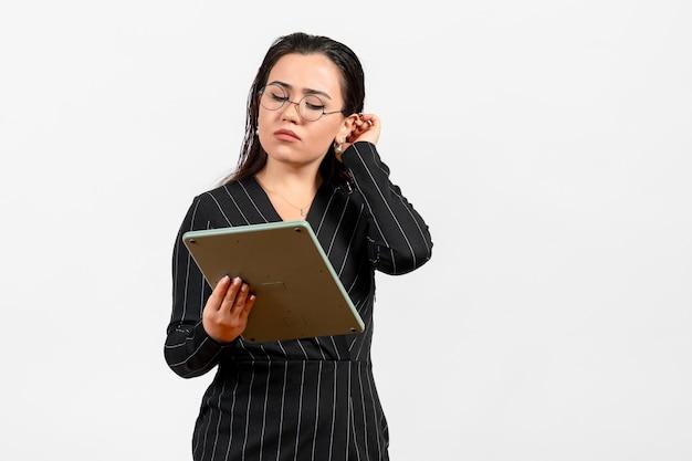 正面図白い背景の仕事の女性の女性の美容ファッションビジネスで巨大な計算機で作業している暗い厳格なスーツの若い女性