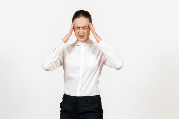正面図白い背景の上の痛みを伴う顔を持つエレガントな白いブラウスの若い女性オフィスの仕事女性労働者の女性