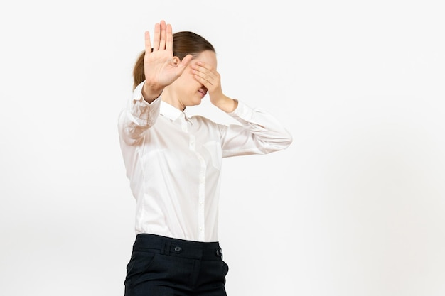 白い背景の上の彼女の顔を覆う白いブラウスの正面図若い女性オフィスの仕事女性の感情感モデル