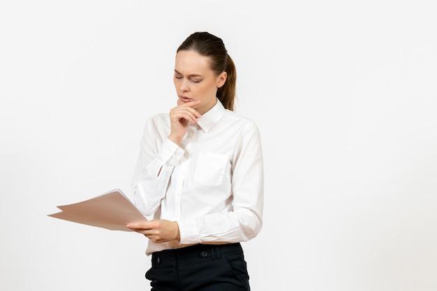 Вид спереди молодая женщина в белой блузке, держащая и читающая документы на белом фоне, женская работа, эмоция, чувство, офис